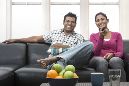 south asian ethnicity: Happy Indian couple on the sofa watching tv in the living room Stock Photo