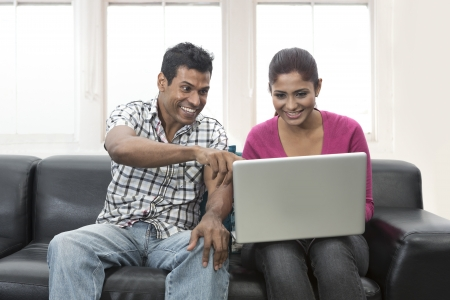 Indian couple relaxing on the sofa with a laptop in their living room at home photo