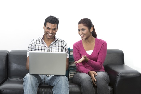 indian couple: Indian couple relaxing on the sofa with a laptop in their living room at home