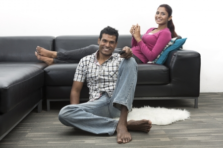 indian ethnicity: Happy Indian couple on the sofa watching tv in the living room Stock Photo