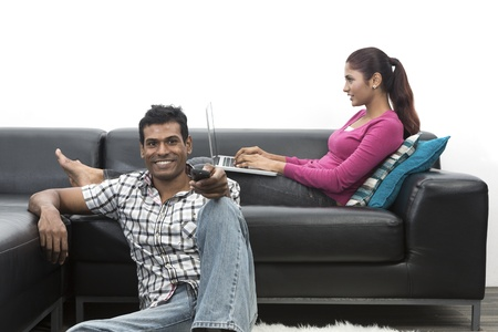 Happy Indian couple on the sofa watching tv in the living room Stock Photo - 19871405