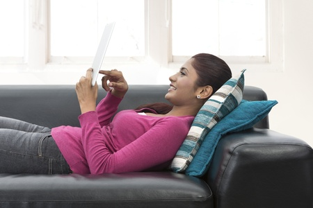 south asian ethnicity: Portrait of a happy Indian woman sitting on sofa using Digital Tablet