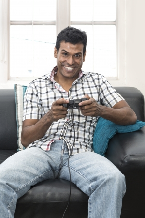 south asian ethnicity: Portrait of an Indian man sitting on couch playing video games