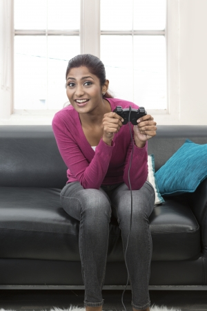 Happy Young Indian woman playing video games on sofa at home Stock Photo - 19871494