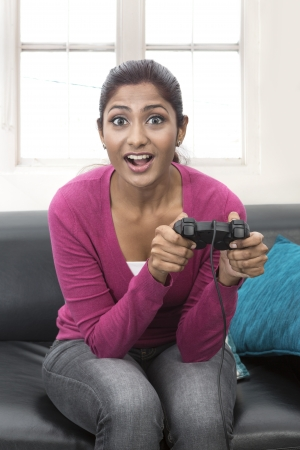 south asian ethnicity: Happy Young Indian woman playing video-games on sofa at home