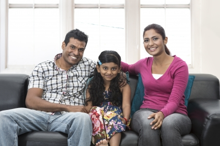 Happy Indian family at home with there child sitting on sofa. photo