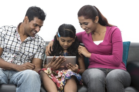 Happy Indian family at home using digital touchpad tablet together on sofa. photo