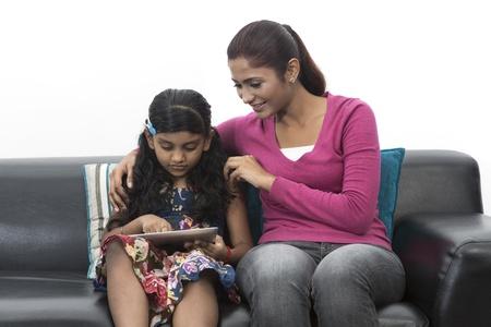 parentalidade: M�e indiana e filha que usa o touchpad digitais em casa no sof�