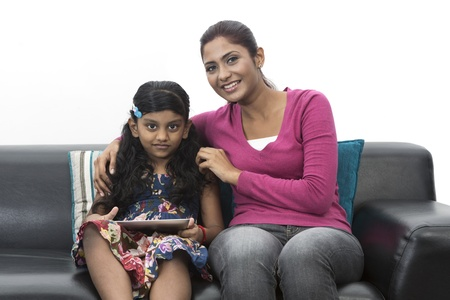 south asian: Indian Mother And Daughter Using digital touchpad At Home on sofa