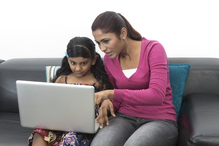 Indian Mother And Daughter Using Laptop At Home on sofa photo