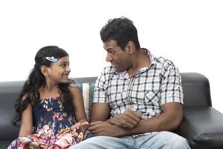 Heureux père indien et sa fille à la maison sur le canapé ensemble.