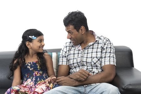 ni�os hablando: Padre indio e hija felices en su casa en el sof� juntos.