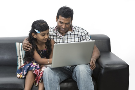 Indian father and daughter at home using a laptop together on the sofa. photo