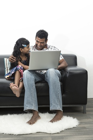 Indian Father and daughter working together on a laptop at home photo