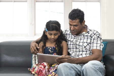 Indian father and daughter at home using digital touchpad tablet together on sofa. photo