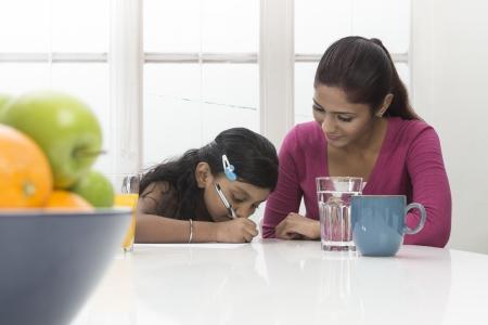 madre trabajando: Mujer india joven ayudando con la tarea. Madre e hija concepto.