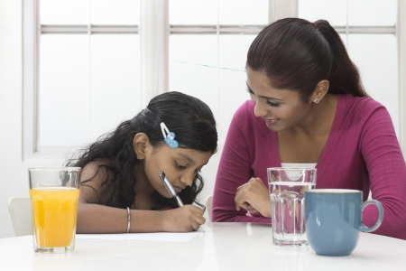 Indian Woman helping young girl with homework at table. Mother and daughter concept. photo
