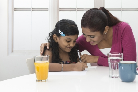 Indian Woman helping young girl with homework at kitchen table. Mother and daughter concept. photo