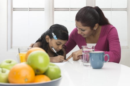 Indian Woman helping young girl with homework at kitchen table. Mother and daughter concept.