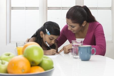 jornada de trabajo: Mujer india joven ayudando con la tarea en la mesa de cocina. Madre e hija concepto.