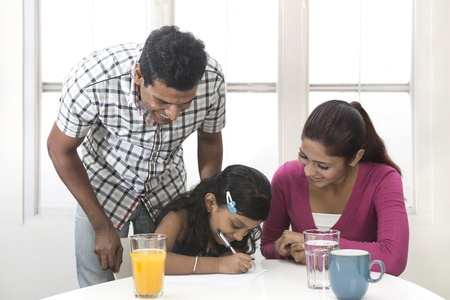 Indian parents helping their child with her home work. Indian family in kitchen relaxing together. photo