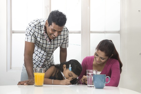 south asian ethnicity: Indian parents helping their child with her home work. Indian family in kitchen relaxing together.