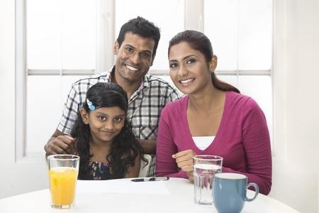 Parents indiens aider leur enfant avec son travail à domicile. Famille indienne dans la cuisine de détente ensemble.