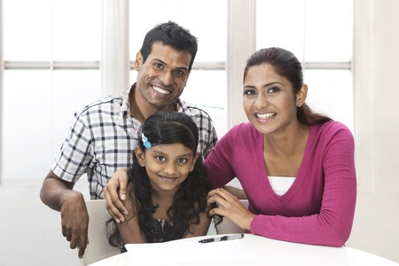 family on couch: Portrait of a Indian family in kitchen relaxing together. Stock Photo