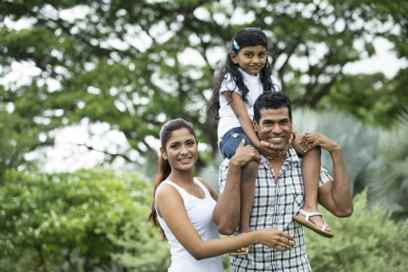 Happy Indian family. Father, mother and daughter in the park photo