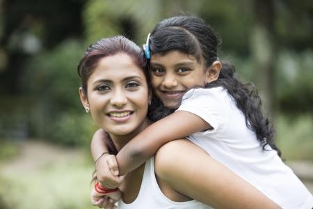 mama e hija: Feliz madre india con su hija jugando en el parque. Imagen de estilo de vida. Foto de archivo