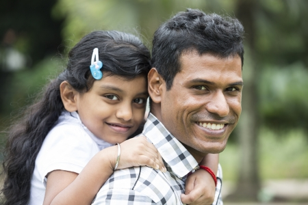 Happy Indian Father and daughter playing in the park. Lifestyle image. photo