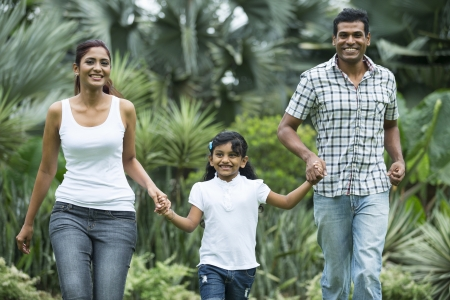 familia saludable: Familia india feliz que se ejecuta junto al aire libre en el parque