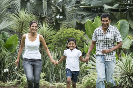 asian family outdoor: Happy indian family running together outdoors in the park