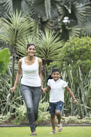 Happy Indian mother and daughter playing in the park. Lifestyle image. photo