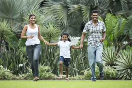healthy asian family: Happy indian family running together outdoors in the park
