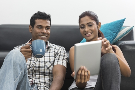 Indian couple relaxing with a digital tablet in their living room photo
