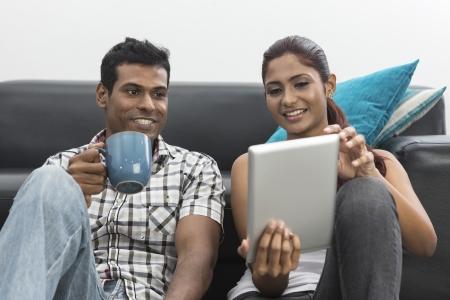 Indian couple se détendre avec une tablette numérique dans leur salon