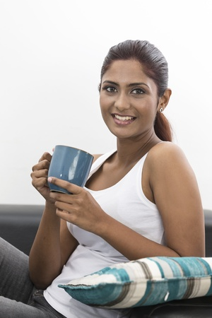 Beautiful young Indian woman relaxing on the sofa at home with a coffee photo
