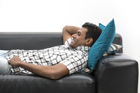 Happy young Indian man relaxing on sofa at home photo
