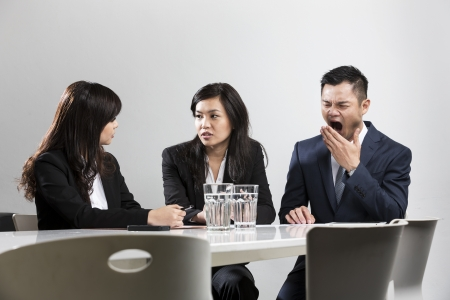 Chinese business man yawning during a business meeting in front of work colleges