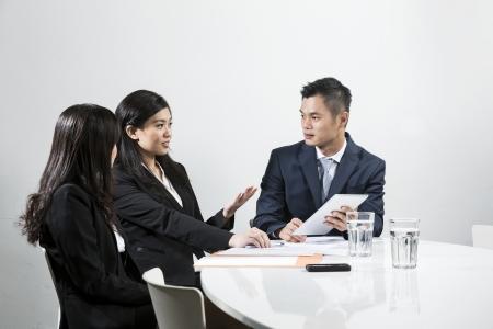 Un groupe de gens d'affaires chinois ayant réunion ensemble