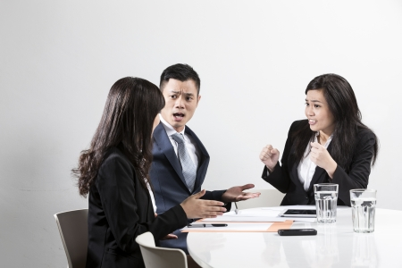 Angry Chinese business man shouting at his colleague in a business meeting photo