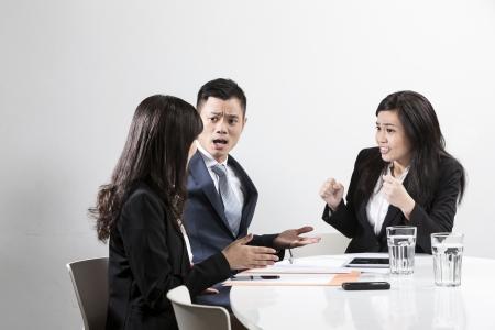 Angry homme d'affaires chinois en criant à son collègue lors d'une réunion d'affaires