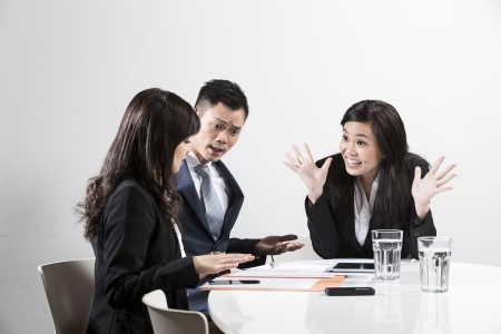 Angry Chinese businesswoman shouting at her colleagues in a business meeting photo