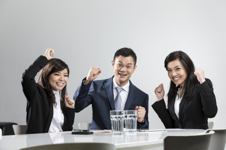 Happy Chinese business people celebrating in a meeting. Concept about success and achivement. photo