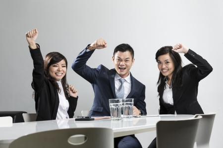seminar room: Happy Chinese business people cheering in a meeting. Concept about success and achivement. Stock Photo