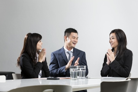 Happy Chinese business people applauding in a meeting. Concept about success and achivement. photo