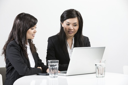 three people only: Two Chinese business women people having a meeting together