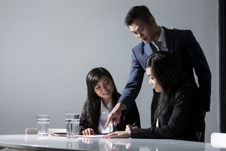 Three Chinese Business people meeting in office to discuss a project Stock Photo - 20058026