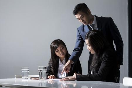 dirección empresarial: Tres personas Chino Reunión de negocios en la oficina para discutir un proyecto